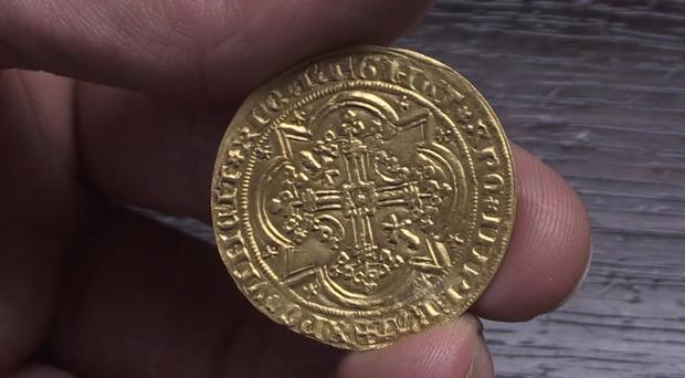 A 14th century French gold coin was found in a secret drawer of a 20th century wooden bureau. The Raymond IV Prince of Orange Franc A Pied coin dates back to 1365. (Phil Barnett/PA Images)