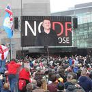 Tommy Robinson seen on the big screen as he addresses a protest against the BBC (Danny Lawson/PA)