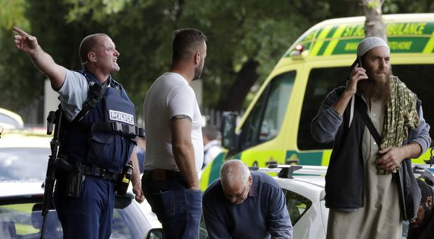 Police attempt to clear people from outside a mosque in central Christchurch (Mark Baker/AP)