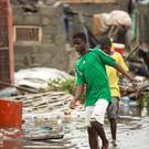 People walk through floodwater in Mozambique in the aftermath of Cyclone Idai (Red Cross/PA)