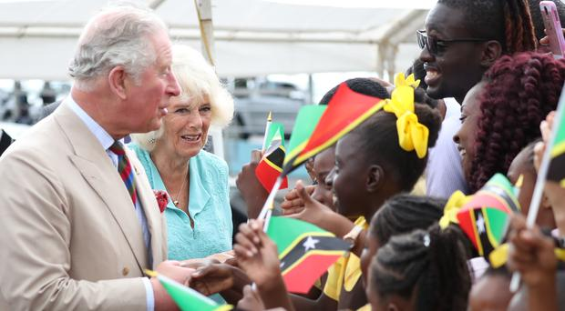 The Prince of Wales and the Duchess of Cornwall are welcomed at Charlestown Pier, Nevis (Jane Barlow/PA)