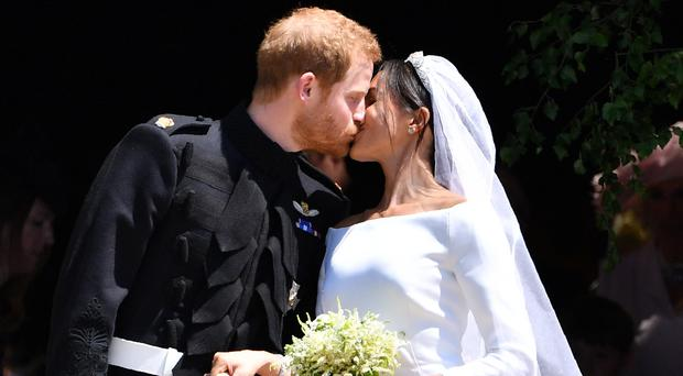 The Duke and Duchess of Sussex kiss as they leave at St George's Chapel in Windsor Castle after their wedding ceremony (Ben Stansall/PA)