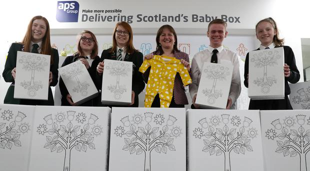 Children's minister Maree Todd meets young people l-r Emily Wilson, Demi Burnett,Holly Henry,Childrens minister Maree Todd,Sonny Robertson and Edith Macdonald who were all involved in the new design of the baby box unveiled at the APS Group in Edinburgh (Andrew Milligan/PA)