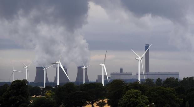 Switch from coal to renewables such as wind and biomass is helping drive fall in UK emissions (John Giles/PA)
