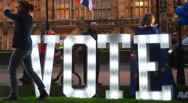 """Anti-Brexit protestors with an illuminated sign reading 'Let Us Vote' outside the Houses of Parliament, London, on the day that MPs will be asked to consider a range of alternative Brexit options after Parliament seized control of the Commons agenda to force a series of """"indicative votes""""."""