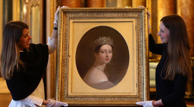 Buckingham Palace staff holding a portrait of Queen Victoria by Thomas Sully, dated 1837-9, during the preview for the Queen Victoria's Palace exhibition for the Summer Opening of Buckingham Palace (Yui Mok/PA)