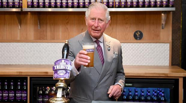 The Prince of Wales pulls a pint of Tribute during a visit to St Austell Brewery in Cornwall (Finbarr Webster/PA)