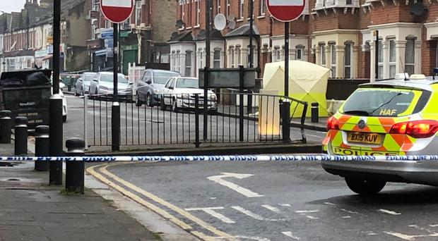 Police at the scene where a man in his 20s died of gunshot and stab wounds in east London (PA)
