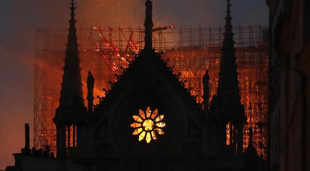 The fire has spread to one of Notre Dame's two towers (AP)