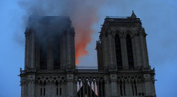 Smoke and flames fill the sky as a fire burns at the Notre Dame Cathedral (Philippe Wojazer/Pool via AP)