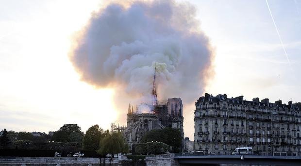 Massive plumes of smoke fill the air above Notre Dame Cathedral (Diana Ayanna/AP)