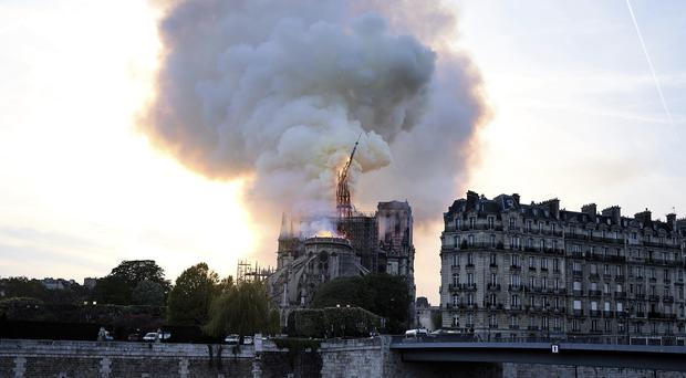 Flames and smoke rise as the spire on Notre Dame cathedral collapses in Paris (Diana Ayanna/AP)