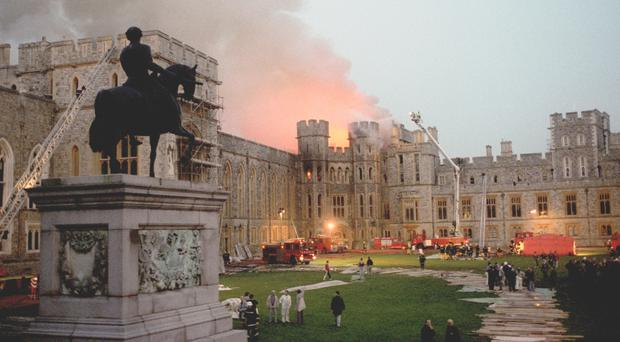 The scene at Windsor Castle in 1992 as dusk falls after the fire swept through the royal home (PA)