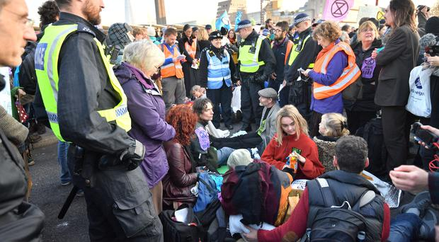 Police with demonstrators on Blackfriars Bridge in London at a protest called by Extinction Rebellion to raise awareness of the dangers posed by climate change.