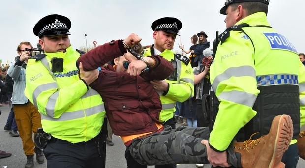 A demonstrator is carried away by police during the second day of an Extinction Rebellion protest on Waterloo Bridge in London (Kirsty O'Connor/PA).