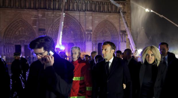 French President Emmanuel Macron, pictured at the scene of the fire, has set a target of five years for Notre Dame to be rebuilt (Philippe Wojazer/AP)