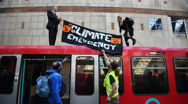 Climate activists on top of a Dockland Light Railway at Canary Wharf station in east London as part of the ongoing climate change protests in the capital (Kirsty O'Connor/PA)