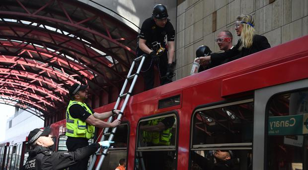 Police remove climate change activists who climbed on top of a train (Kirsty O'Connor/PA)