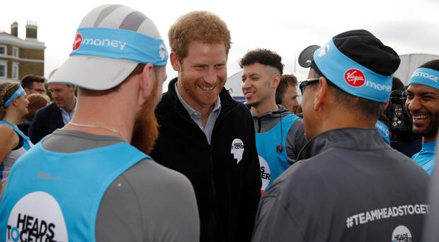 Harry with runners representing the charity 'Heads Together' before officially starting the Virgin Money London Marathon in 2017 (Luke MacGregor/PA)