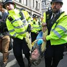 An Extinction Rebellion demonstrator is carried away by police at Oxford Circus (Jonathan Brady/PA)