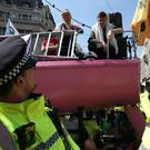 Police surround the Extinction Rebellion boat as Emma Thompson (centre left) joins demonstrators (Jonathan Brady/PA)