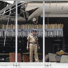 A Sri Lankan Police officer inspects a blast spot at the Shangri-la hotel in Colombo (Eranga Jayawardena/AP)