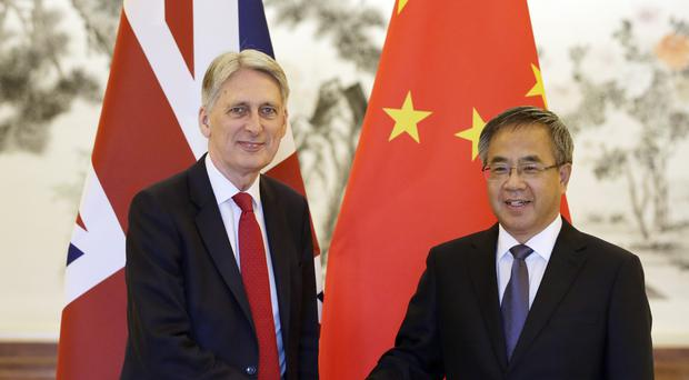 Britain's Chancellor of the Exchequer Philip Hammond, left, meets Chinese Vice Premier Hu Chunhua at Diaoyutai State Guesthouse in Beijing, China, (Jason Lee/Pool Photo via AP)