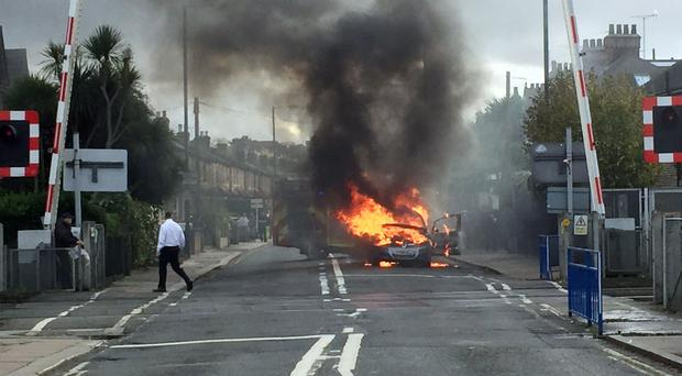 Firefighters extinguish a Vauxhall Zafira which caught light near a level crossing in London (Laura Kerr/PA)
