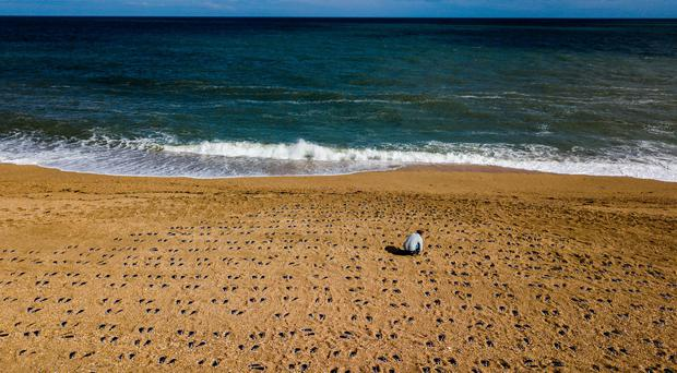 Artist Martin Barraud working on an installation of 749 pairs of bootprints at Slapton Sands, Devon (There But Not There/PA)