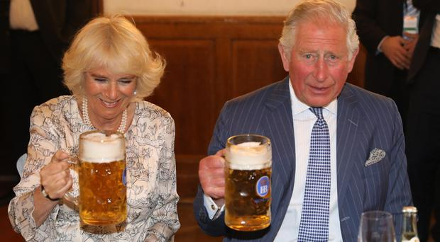 The Prince of Wales and the Duchess of Cornwall enjoy beer steins at a traditional dance and beer hall in Munich, Germany (Steve Parsons/PA)