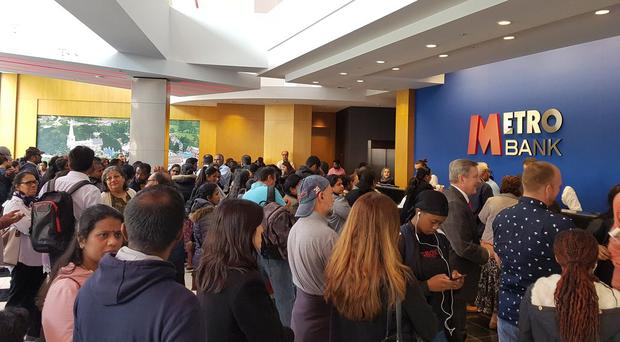 A large crowd turned up at Metro Bank in Harrow to withdraw funds after the false rumours (Patrick O'Brien/PA)
