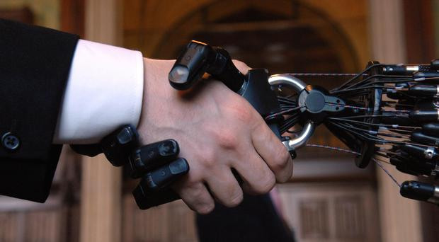 A person shakes hands with Shadow Robot Company's C5 Dexterous Hand (Tim Ireland/PA)