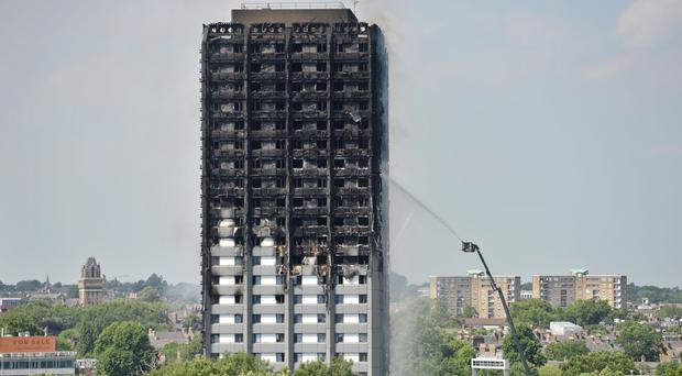"""Firefighters spraying water after the fire engulfed Grenfell Tower in west London. Grenfell families have hit out at the """"amnesia fix"""" of corporations during the public inquiry, and called the delay in bringing in urgent fire safety recommendations a farce."""