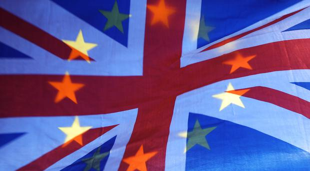 An EU and Union flag held aloft in Westminster, London.