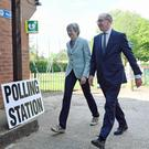 Theresa May and her husband Philip arrive to cast their votes at a polling station near her Maidenhead constituency (Victoria Jones/PA)