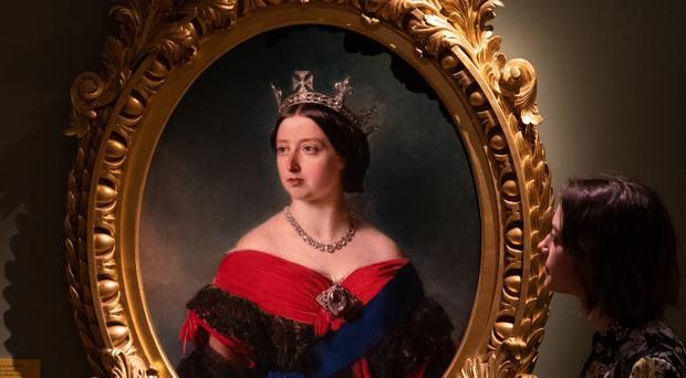 A gallery employee looks at a portrait of Queen Victoria by Franz Winterhalter 1856 at the Victoria: Woman and Crown exhibition at Kensington Palace (Aaron Chown/PA)
