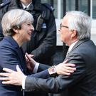 Theresa May greets Jean-Claude Juncker ahead of a working dinner (John Stillwell/PA)
