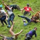 Participants take part in the annual cheese rolling competition at Cooper's Hill in Brockworth (Ben Birchall/PA)