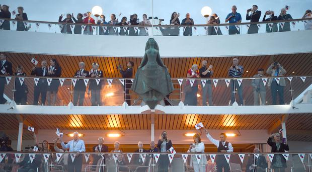 Veterans and crew members wave flags from the MV Boudicca (Kirsty O'Connor/PA)