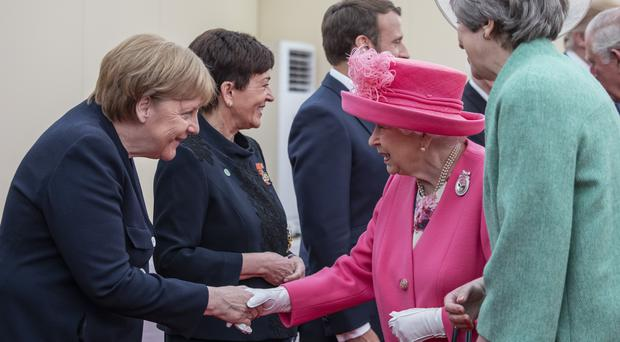 The Queen shakes hands with German chancellor Angela Merkel as Theresa May watches on (Jack Hill/The Times/PA)