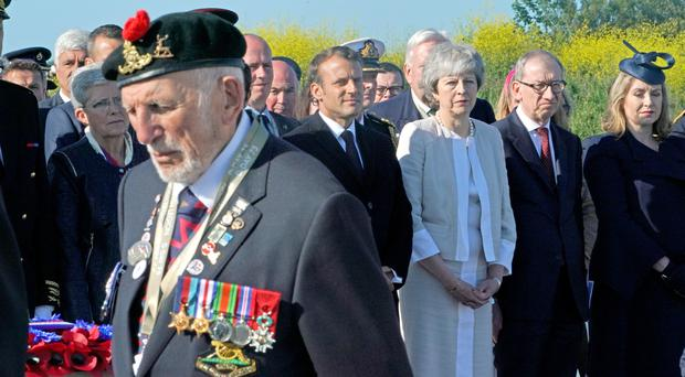 A D-Day veteran passes French President Emmanuel Macron and Prime Minister Theresa May at the inauguration of the British Normandy Memorial site in Ver-sur-Mer, France (Owen Humphreys/PA)