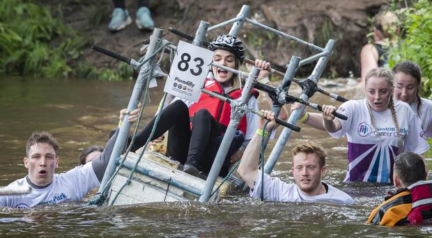 Competitors cross the River Nidd (Danny Lawson/PA)