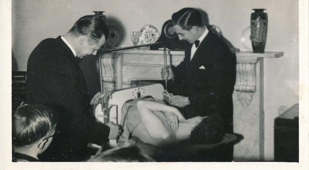 Magician Cyril Bayliffe (right) demonstrating one of his famous knife tricks on his reluctant daughter. (PA/Hansons)