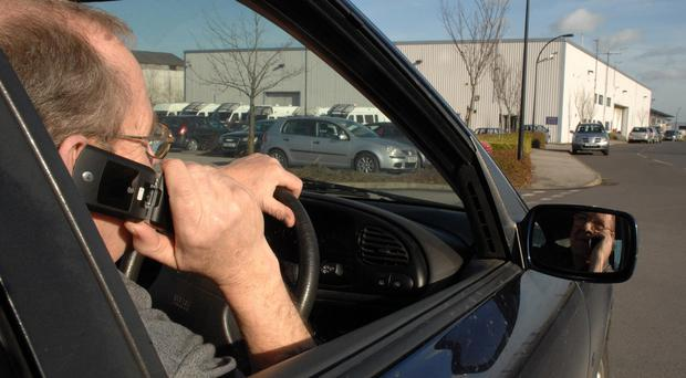 Picture posed by a model of a driver talking on his mobile phone while driving (Anna Gowthorpe/PA)
