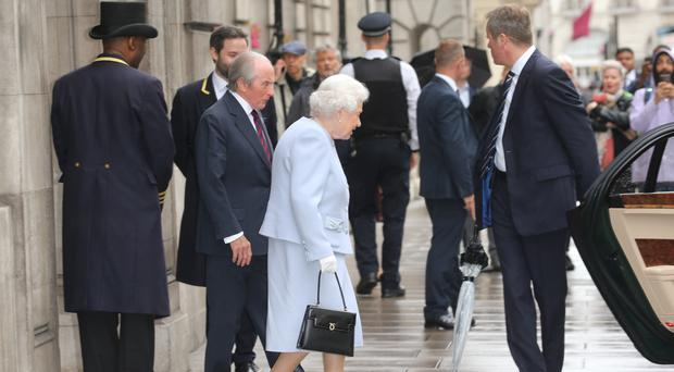 Sir Jackie Stewart escorts the Queen to her car outside the RAC Club in Pall Mall (Isabel Infantes/PA)