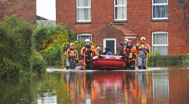 Residents are taken to safety in an inflatable boat by rescue workers in Wainfleet All Saints, in Lincolnshire (Joe Giddens/PA)