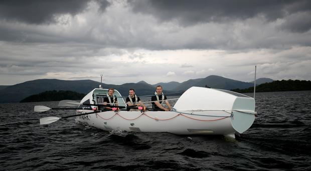 Brothers (from left) Lachlan, 21, Ewan, 27, and Jamie MacLean, 25, from Edinburgh, try out their boat on Loch Lomond for the first time before they row 3000 miles across the Atlantic Ocean in a charity challenge (Jane Barlow/PA)