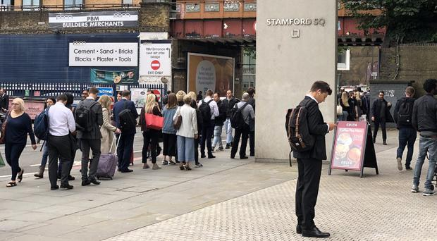 Commuters stand in line at East Putney station on Wednesday (Tim Rye/PA)