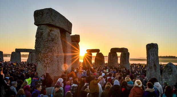 The sun rises between the stones and over crowds at Stonehenge (Ben Birchall/PA)