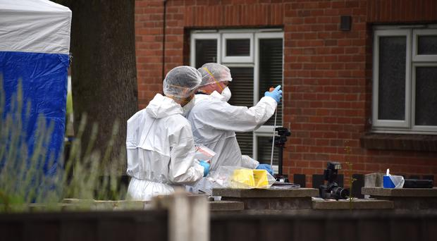 Forensic officers near the entrance to a flat following the death of a man in a fire (Matthew Cooper/PA)